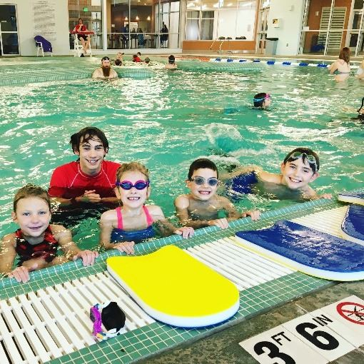 Four children and a lifeguard in the pool learning to swim