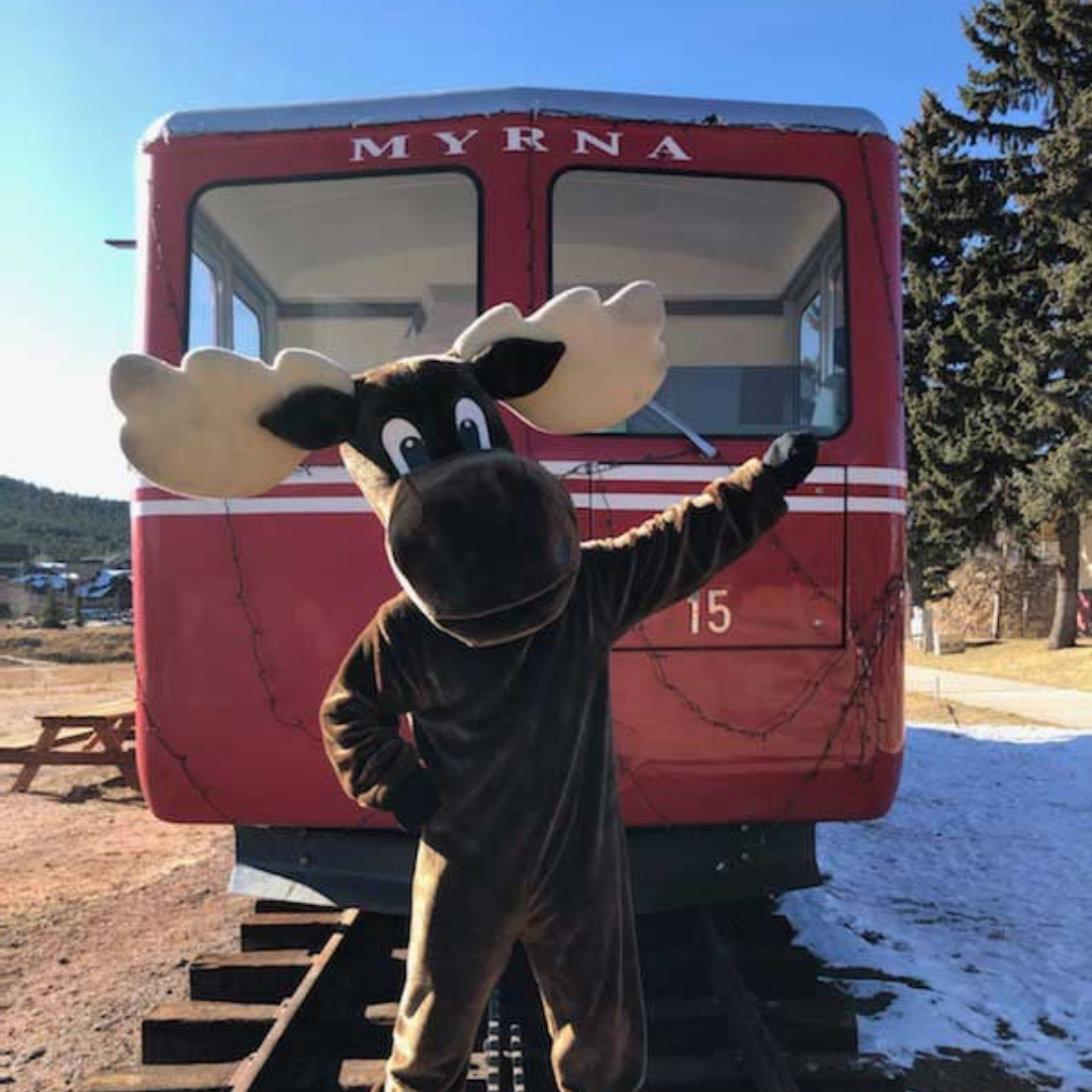 Person in Moose Costume standing in front of red cog railway car